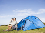 Man camping outdoors and looking through binoculars